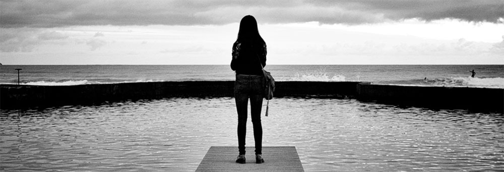 A sad girl standing on a pier