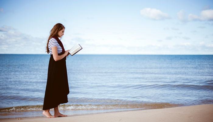 a-woman-is-reading-the-bible-on-the-beach